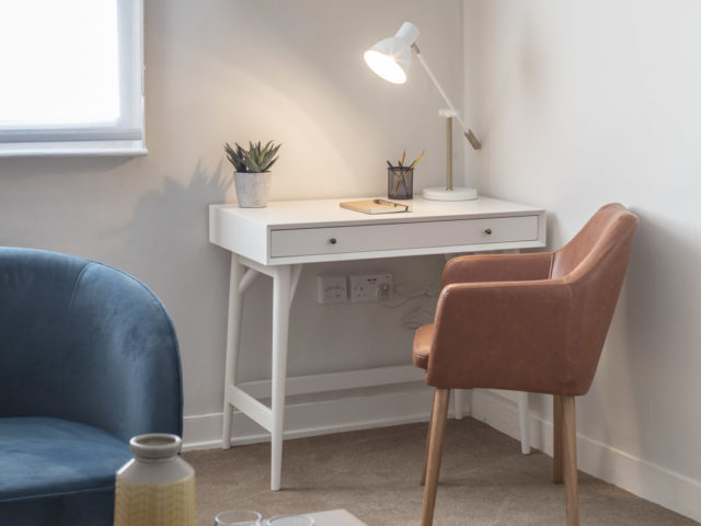 Counselling room with desk and pastel colour scheme