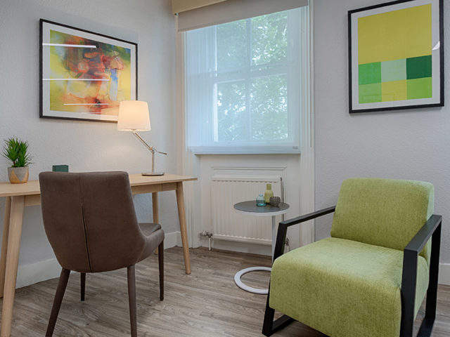 Spacious therapy room with office desk and comfortable client chairs